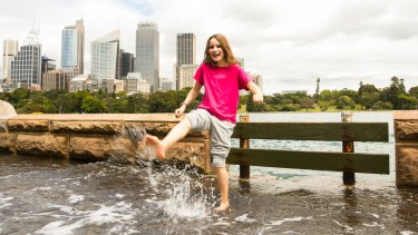 Ten-year-old Poppy Rudge from the UK wades through the water at the Botanic Gardens while her family watches.