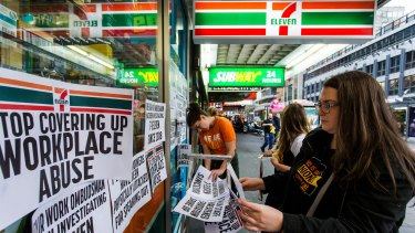 Protesters from the Young Workers Centre pin signs to the windows of 7-Eleven at a protest on Wednesday.