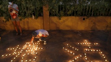 People light candles during a candlelight vigil for victims of Wednesday night's explosions.