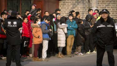 Chinese police watch as depositors from Ezubao gather outside the State Bureau for Letters and Calls Reception Division office in Beijing in early January.