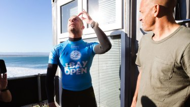 Mick Fanning looks to the skies in thanks after explaining to Kelly Slater (right) what he went through.