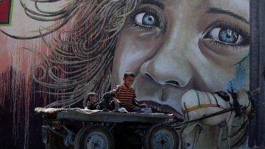 Two Palestinian boys play on a donkey cart  in Deir el-Balah refugee camp, central Gaza Strip.