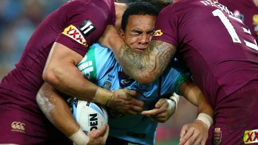 Crunched: Blues winger Will Hopoate is squeezed by the Queensland defence.