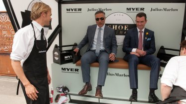 Ahmed Fahour (left), taking advantage of a free shoe shine at the 2015 Melbourne Cup.