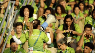 Olympic Park workers listen to instructions before the start of the Rio 2016 Summer Olympics.