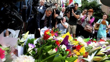 NSW Premier Mike Baird lays flowers at Martin Place after the seige where three people died early on Tuesday morning.