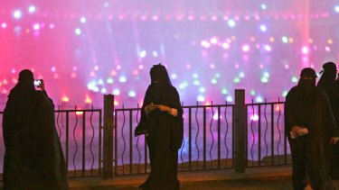 A Saudi woman takes photographs in a park during celebrations to mark the worldwide Earth Hour in Riyadh, Saudi Arabia.