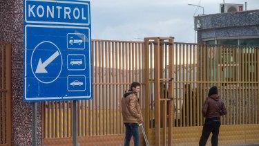 People wait outside a closed Turkish-Syrian border gate in Killis on Sunday.