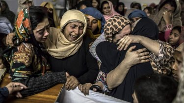 Female relatives mourn over the coffin of 15-year-old Mohammed Ali Khan after the school massacre in Peshawar.