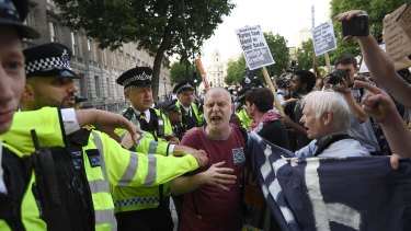 A scuffle breaks out as protesters attend a rally calling for justice for those affected by the Grenfell Tower fire outside Prime Minister Theresa May on Friday.