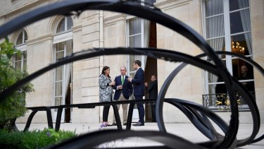 French President Emmanuel Macron, right, Paris Mayor Anne Hidalgo, left, and former mayor of New York City Michael Bloomberg talkat the Elysee Palace in Paris on Friday.
