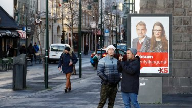 Icelanders walk past a social democrats election poster in Reykjavik, Iceland on Thursday.