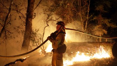 A firefighter holds a water hose while fighting a wildfire on Saturday.