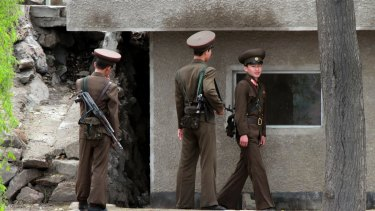 North Korean soldiers stand guard outside their post along the river bank of the North Korean town of Sinuiju, opposite the Chinese border city of Dandong in March.