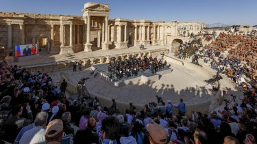 The concert in Palmyra, with the screen showing Vladimir Putin live via video link on the left.