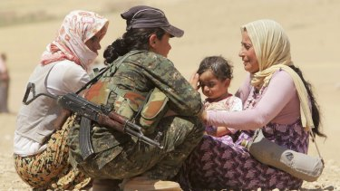 Displaced people from the minority Yazidi sect, fleeing Islamic State forces in the Iraqi town of Sinjar, get help from a member of the Kurdish YPG militia in August of last year.