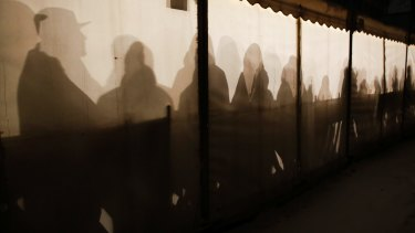 Migrants are silhouetted as they warm themselves inside a waiting tent to get an appointment at the central registration centre for refugees and asylum seekers in Berlin in 2016.