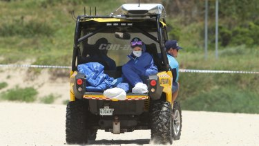 Police Forensic Services take the baby's body off the beach.