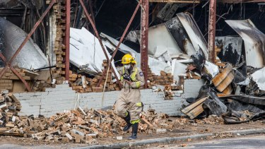 A firefighter walks past the gutted remains of the Little Saigon Market.