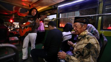 'Ho' entertains commuters on a bus.