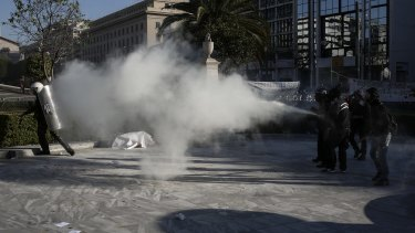 A protester sprays a fire extinguisher at riot police during a rally in front of the Athens University, on Thursday.