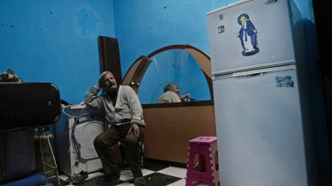 Ezzat Yaacoub Ishak, who fled Arish due to fighting, sits in his newly rented apartment in Ismailia.