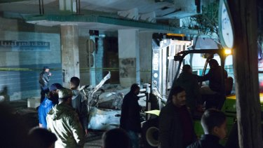 Security officers supervise as a forklift moves a car that exploded near the Italian embassy in Tripoli on Saturday.
