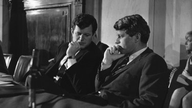 Edward Kennedy, who saw two brothers assassinated by guns, sits with Robert Kennedy in 1967.