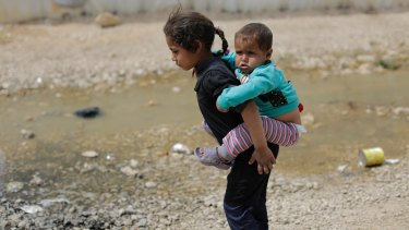 Uncertain future: A Syrian refugee girl holds her brother at the al-Marj camp in Lebanon's Bekaa Valley.