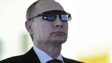 Russian President Vladimir Putin wears special glasses at a research facility in St Petersburg