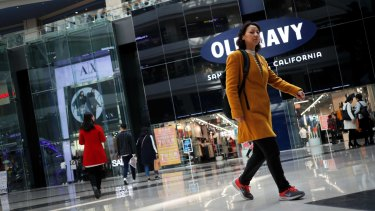 People walk near foreign brands fashion outlets at a shopping mall in Beijing. China is offering a reward for CHinese nationals to dob in foreign spies.