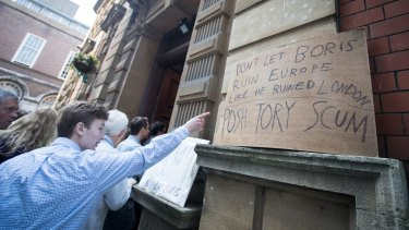 Protest signs are displayed as people queue to listen to Conservative MP Boris Johnson in Bristol on Saturday.