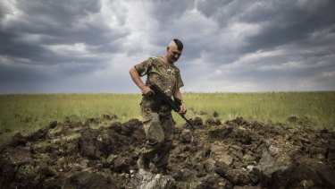 A Ukrainian serviceman investigates the crater left by a Grad rocket in the  Luhansk region in eastern Ukraine, on Monday.