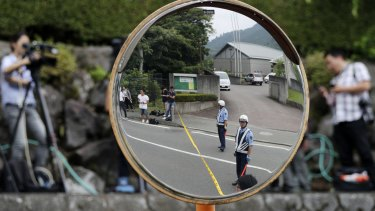 Police officers standing guard are reflected on a road mirror near the Tsukui Yamayuri-en, a facility for the disabled in Sagamihara, outside of Tokyo, Japan, on Tuesday.