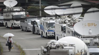 A woman walks by a line of outside broadcasting vans parked near the Tsukui Yamayuri-en facility.