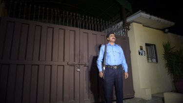 A Pakistani policeman stands guard outside the Islamabad office of the international charity Save the Children, which was sealed by order of Pakistani authorities on June 11.