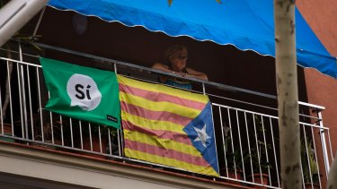 A woman looks out from her balcony decorated with an Estelada or pro-independence Catalan flag and a banner calling for a Yes vote.
