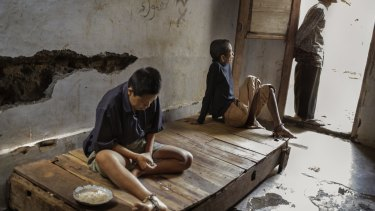 Two residents at the Bina Lestari healing centre in Brebes, Central Java, are chained to a wooden platform bed while an Islamic faith healer stands nearby.