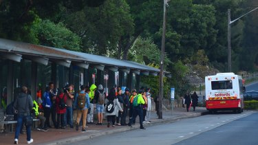 Commuters wait for a bus at Strathfield train station during the bus strike.
