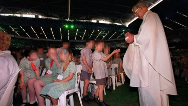 Father Joseph Doyle administers Mass to school children in 2000 at a huge celebration at the Docklands stadium in Melbourne.