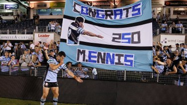 Sharks fans love their No.9: Michael Ennis celebrates with fans in front of a banner made to celebrate his 250th NRL game in March.