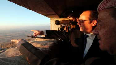 French President Francois Hollande and Massoud Barzani, right, President of the Iraqi self-ruled Kurdish region, point towards IS-held territory on the outskirts of Mosul.