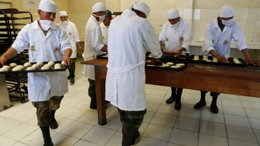 Bolivian soldiers make bread at the Miraflores army barracks in La Paz, Bolivia, on Tuesday.