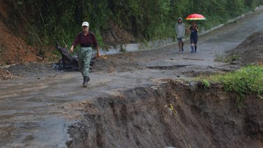 Neighbours walk past a collapsed road in Alajuelita on the outskirts of San Jose, Costa Rica.