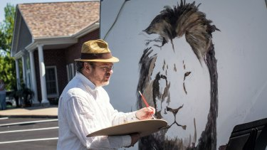 Artist Mark Balma paints a mural of Ceci outside Walter Palmer's office in Bloomington, Minnesota, on Wednesday.