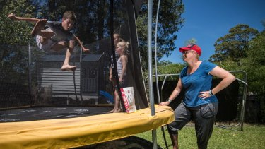 Dimity Statheos watches her children, Silas and Karis with neighbour Lydia, on their new trampoline with their old trampoline in the background.