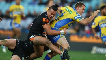 Western derby: Parramatta forward Danny Wicks is tackled by Wests Tigers rival Sauaso Sue.