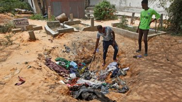 Afrah Ibrahim, centre, searches through the clothes of the dead for a clue to his missing sister outside a hospital in Mogadishu.