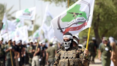 Members of the Shiite group Asaib Ahl al-Haq march in Baghdad in July.