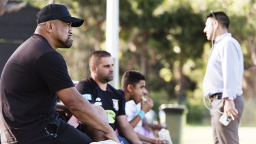 Sidelined: John Hopoate watches from the sidelines as Manly's SG Ball team trains last week.